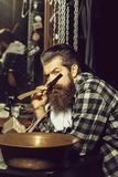 Bearded man shaves with razor. Handsome man, bearded hipster, brunette with long beard and moustache shaves with open vintage razor with blade and copper basin stock photography