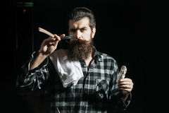 Bearded man shaves with razor. Handsome man, bearded hipster, brunette with long beard and moustache shaves with open vintage razor with blade and shaving brush stock photography