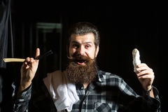 Bearded man shaves with razor. Happy man, handsome, bearded hipster, brunette with long beard and moustache shaves with vintage razor with open blade and shaving stock photo