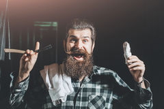 Bearded man shaves with razor. Happy man, handsome, bearded hipster, brunette with long beard and moustache shaves with vintage razor with open blade and shaving royalty free stock photography