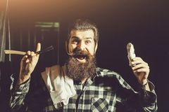 Bearded man shaves with razor. Happy man, handsome, bearded hipster, brunette with long beard and moustache shaves with vintage razor with open blade and shaving royalty free stock photos