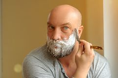A bearded man shaves with a straight razor.  stock photography