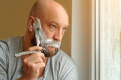 A bearded man shaves with a straight razor stock photos