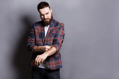 Bearded man in shirt adjusting sleeves copy space Royalty Free Stock Image