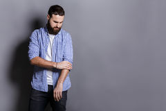 Bearded man in shirt adjusting sleeves copy space Stock Photography