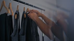 Bearded Man is Shopping Choosing a Suit on Rack in Men`s Fashion Clothing Store. Young Bearded Man is Choosing Vest among Men`s Suits on Hangers on a Rack in stock footage