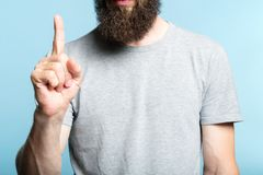 Bearded man show hand number one counting gesture stock photo