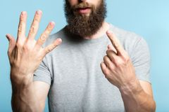 Bearded man show hand number six counting gesture. Bearded man showing number six with his hand. cropped shot of a male torso on blue background. casual hipster royalty free stock image