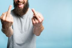 Man middle finger defiance offensive attitude. Bearded man showing middle fingers. provocation defiance attitude and offensive indecent behavior concept. cropped stock image