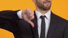 Bearded man showing thumbs-down, dislike, negative feedback about service