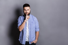 Bearded man shows hush be quiet. Handsome guy holding finger at his lips, gray studio background, copy space. Secret, privacy concept Royalty Free Stock Photography