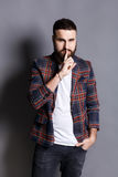 Bearded man shows hush be quiet. Handsome hipster holding finger at his lips, gray studio background, copy space. Secret, privacy concept Stock Image