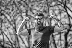 Bearded man shows muscles, biceps on sunny day. Masculinity concept. Man with long beard looks energetic and cheerful. Man with beard and mustache on happy stock images