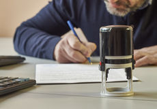 Bearded man signs a contract. Middle-aged businessman sitting at office desk and signing a contract stock photography