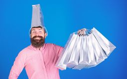 Bearded man with silly look and big smile isolated on blue background. Male shopaholic with trendy beard carrying silver. Papper bags. Shop-assistand promoting stock image