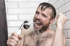 Bearded man singing in the bathroom using the shower head with f. Cute bearded man singing in the bathroom using the shower head with flowing water instead of a royalty free stock image