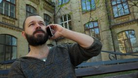 The bearded man sits on a bench in a city park and talks on the phone during his trip stock video footage