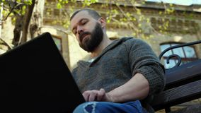 The bearded man sits on a bench in the park, prints text on a laptop stock video footage