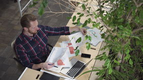 The bearded man sits in the environmental office and looks at the figures on paper. stock footage