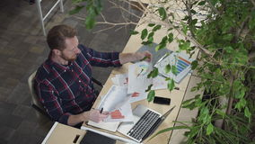 The bearded man sits in the environmental office and looks at the figures on paper. stock video