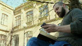 The bearded man sits in a park and reads a book, but he receives a phone call stock footage