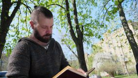 The bearded man sits in the park and reads an interesting book stock video footage