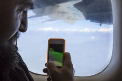 Bearded man sitting at airplane window and taking photo on telephone Stock Photo