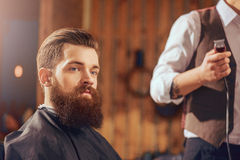 Bearded man sitting in the barbershop. Like the result. Bearded handsome men sitting in the barbershop while barber standing with electric razor nearby Royalty Free Stock Photography