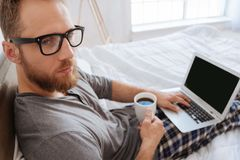Bearded man sitting on bed with coffee and laptop Stock Photos