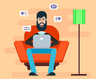Bearded man sitting in a chair with a laptop on his lap and browsing Internet. Home cozy atmosphere. Comfortable domestic illustration Stock Images