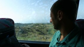 Bearded man sitting on coach and watching through window at changing landscape. Stock footage stock footage