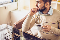 Bearded man sitting with cup of morning coffee and looking out the window stock photos