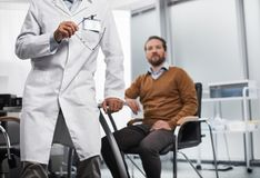 Bearded man is sitting at doctor office stock image