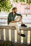 Bearded man sitting on fence in city under the trees Stock Photos