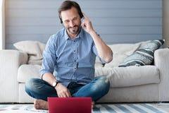 Bearded man sitting on floor with headphones using laptop Royalty Free Stock Photos