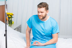 Bearded man sitting on hospital bed with drop counter Royalty Free Stock Photography