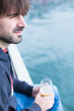 Bearded man sitting near water and holding glass of beer Stock Photos