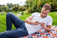 Bearded man sitting in park on blanket. He is using mobile phone Royalty Free Stock Photo