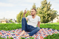 Bearded man sitting in park on blanket. He is using mobile phone Stock Photos