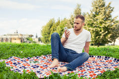 Bearded man sitting in park on blanket. He is using mobile phone Stock Image