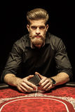 Bearded man sitting at poker table and holding smartphone Stock Photo