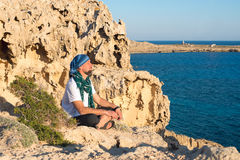 Bearded man sitting on a rocky shore Royalty Free Stock Photo