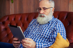 Bearded man sitting on sofa and reading news Stock Images