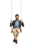 Bearded man sitting on a swing and looking at the camera royalty free stock image