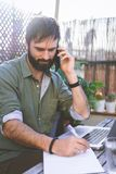 Bearded Man sitting at vintage natural rough wood desk working on laptop computer and using mobile phone at cafe terrace. Surrounded green flores and cactus.Out royalty free stock photography