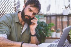 Bearded Man sitting at vintage natural rough wood desk working on laptop computer and using mobile phone at cafe terrace. Surrounded green flores and cactus.Out royalty free stock photos