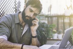 Bearded Man sitting at vintage natural rough wood desk working on laptop computer and using mobile phone at cafe terrace. Surrounded green flores and cactus.Out stock image