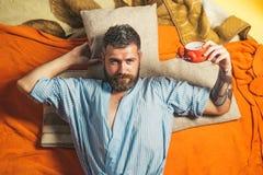 Bearded man sleep on floor with alarm clock. stock photography