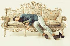 Bearded man sleeping on couch. Handsome bearded young man in blue shirt and jeans sleeping on luxurious couch with flower pattern with book and female shoes royalty free stock photography