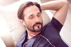 Bearded man sleeping with earphones. Desired rest. Mature bearded man lying on the couch and sleeping while listening to music through earphones Royalty Free Stock Photos